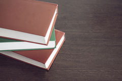 Three books on a wood table. Three books on an empty wooden table Royalty Free Stock Photo