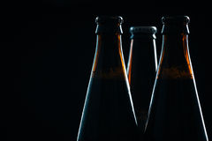 Three bottle of dark beer on a  blurred background Royalty Free Stock Photos