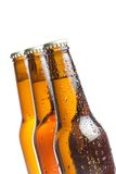Three bottle of fresh beer with drops, isolated Stock Images