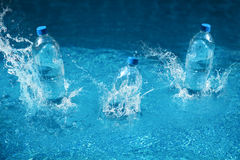 Three bottle of water drop with splash. Shot in motion Stock Photography