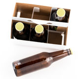 Three bottles of beer with caps and one on side royalty free stock photos