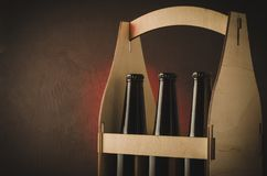 three bottles of beer in a wooden case on a red light background/three bottles of beer in a wooden case on a red light background royalty free stock photos