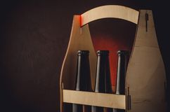 three bottles of beer in a wooden case/beer bottles case on wooden shelf on a red light background. Copyspace stock photography