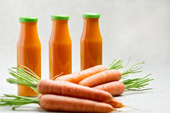Three bottles of carrot juice with carrots. Royalty Free Stock Photos