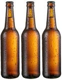 Three bottles of cold beer with big condensate drops. stock photo