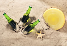 Three bottles of cold beer on sand, top view Stock Photos