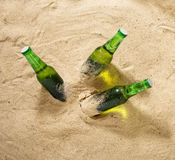 Three bottles of cold light beer on sand Royalty Free Stock Images