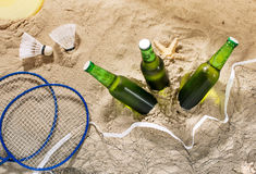 Three bottles of cold light beer on sand, top view Royalty Free Stock Images