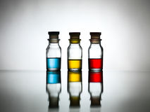 Three bottles with colored solution on table Stock Photo