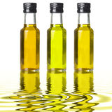 Three bottles of different olive oil on liquid reflections Royalty Free Stock Images