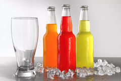 Three bottles with drinks with glass and ice Stock Photo