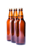 Three bottles of ice cold beer isolated on white Stock Photos