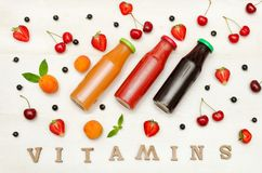 Three bottles with juice, fruit and inscription vitamins on a white background, food concept Royalty Free Stock Photos
