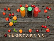 Three bottles with juice, fruit and inscription vitamins on a wooden background, food concept Stock Photo