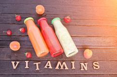 Three bottles with juice, fruit and inscription vitamins on a wooden background, food concept Royalty Free Stock Images