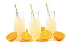 Three bottles of lemonade with lemon slices and straws isolated Stock Photo