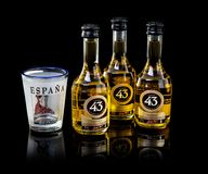 Three bottles of Licor 43 with a shot glass from Spain. SWINDON, UK - SEPTEMBER 22, 2018: Three bottles of Licor 43 with a shot glass from Spain on a back Stock Photography