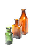 Three bottles in line. A photo of three colorful old style bottles with different shape and height in row in growing order. Two bottles have octagon floor plan Royalty Free Stock Image