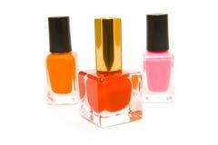 Three Bottles of Nail Polish. Three bottles of red, pink and orange nail polish on a white background Royalty Free Stock Photo