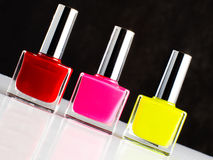 Three bottles of nail polish standing on sloping white surface Royalty Free Stock Photos