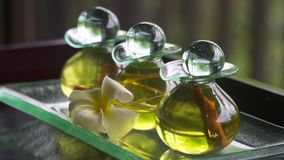 Three bottles of oil on a glass tray. Close up of three bottles of oil resting on a glass tray next to a white flower stock video footage