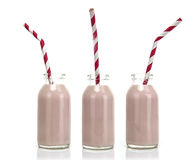 Three Bottles of pink milk with red and white striped straws Royalty Free Stock Photography