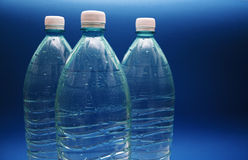 Three bottles of pure water. On blue background Stock Image