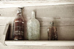 Three bottles on shelf Stock Image