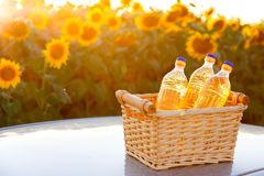 Three bottles of sunflower oil in a wicker basket in sunset Stock Photos