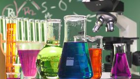 Three bottles of various shapes and colors on a turntable. Ambiance performed with various laboratory containers and a microscope on green chalk board background stock video footage