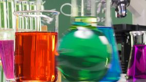Three bottles of various shapes and colors on a turntable. Ambiance performed with various laboratory containers and a microscope on green chalk board background stock footage