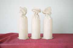 Three Bottles Wrapped In Paper Royalty Free Stock Images