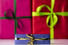 Three bowknots tied around gifts. Magenta and red color-fields of box surfaces in contrast with the shape of green bows. Their soft focus is augmenting the sharp Royalty Free Stock Images