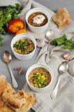 Three bowls of bean, quinoa soup and mushroom bulgur on a gray b Stock Photo