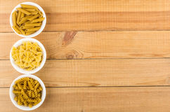 Three bowls with different pasta from left side table Stock Image