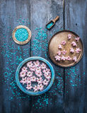 Three Bowls with flowers , sea salt and scoop on blue wooden table, wellness background. Top view Royalty Free Stock Photography