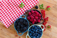 Three bowls of fresh berries. Three bowls of fresh raspberry , bluberry and black berry on wooden table Royalty Free Stock Image