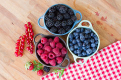 Three bowls of fresh raspberry. On wooden table Stock Photo