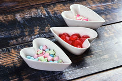 Three bowls with heart shaped candies on shabby background Stock Photo
