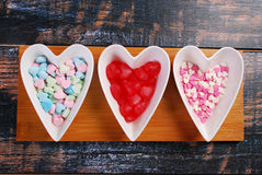 Three bowls with heart shaped candies on shabby background Royalty Free Stock Photography