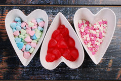 Three bowls with heart shaped candies on shabby background Stock Images