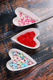 Three bowls with heart shaped candies on shabby background Stock Image
