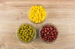 Three bowls with red beans, sweet corn and green peas Stock Images