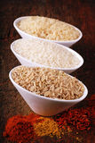 Three bowls with rice and indian spices Stock Photos