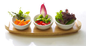 Three bowls of salad. Different varieties of salad in three small bowls placed on a wooden tray Royalty Free Stock Photography