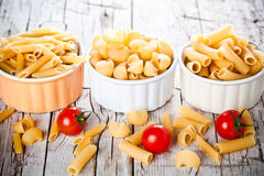 Three bowls with uncooked pasta and cherry tomatoes Stock Photo