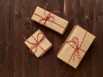 Gifts in kraft paper on a brown wooden background Royalty Free Stock Photos
