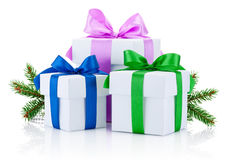 Three boxs tied with colored ribbons bow and pine tree branch Isolated Royalty Free Stock Photography