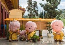 Three boy monk dolls at Hsi Lai Buddhist Temple, California. Hacienda Heights, CA, USA - March 23, 2018: Three funny Boy novice monk paper dolls, yellow and Stock Photography