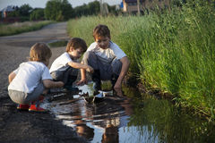 Three boy play in puddle Stock Photo